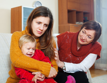 intergenerational: Young mother has trouble. Mature woman comforting adult daughter with baby   at home