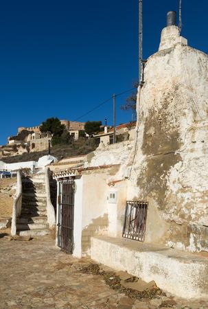 chinchilla: Dwellings caves  with сhimneys  into mount. Chinchilla de Monte-Aragon, Albacete, Spain Stock Photo