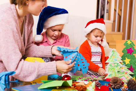 flay: Young woman helping little daughters  to make decoration for Xmas  at home