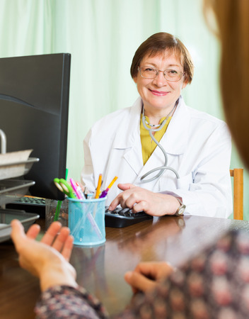 communicates: Elderly woman doctor communicates with patient sitting at computer Stock Photo