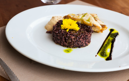 france: Hake with black rice and sauce on white plate at restaurant