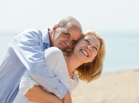 hispanic family: Happy elderly couple at sea vacation smiling and hug together