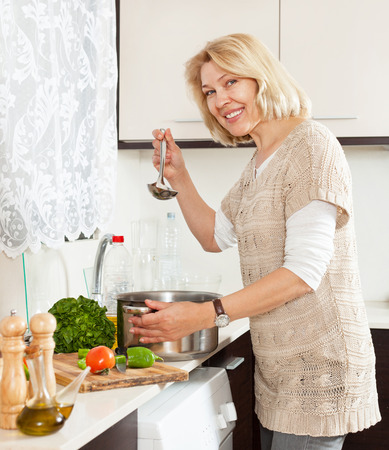 woman cooking: mature  woman  with ladle cooking soup in pan  in kitchen  home  interior Stock Photo