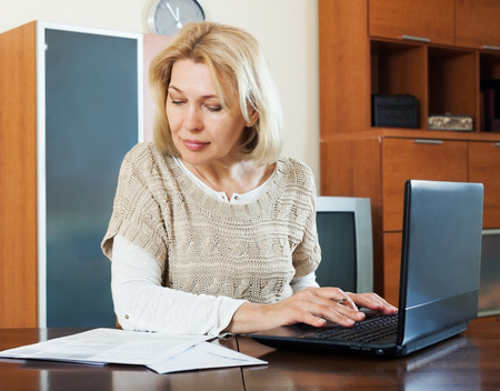 utility payments: serious mature woman with laptop and financial documents at table at home Stock Photo