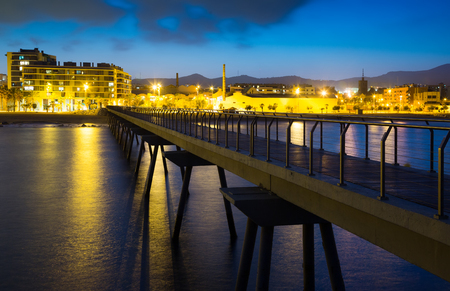 fabrica: Pier and beach in evening.  Badalona, Spain
