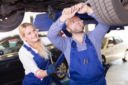 mecanico: americano del hombre mecánico y ayudante femenino que trabaja en la tienda de reparación de automóviles