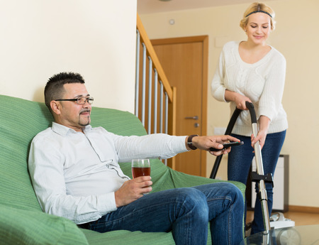 young wife: Happy wife hoovering the room, husband relaxing on a couch Stock Photo