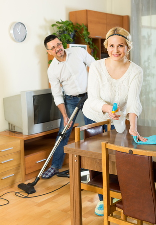 25s: Cheerful husband helping his smiling blonde wife cleaning the room. Focus on woman