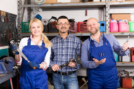 maintenance engineer: Portrait of two cheerful troubleshooters and superviser at auto repair shop