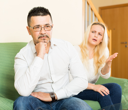 jackboot: Sad guy and  woman during quarrel  in living room at home
