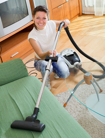 hoover: Smiling female cleaning sofa with hoover at living room