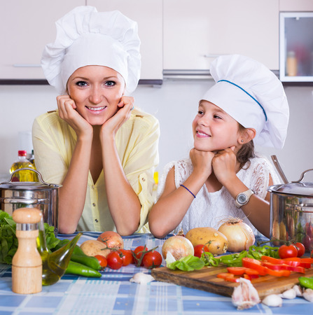 vegeterian: happy spanish mom and little daughter cooking vegeterian dish indoors