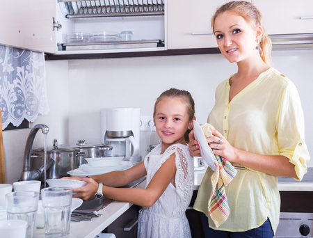 children face: Everyday routine: young russian girls doing and wiping dishes in kitchen