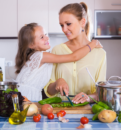 vegeterian: Excited european mom and little daughter cooking vegeterian dish indoors Stock Photo
