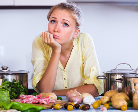 sad lady: Frustrated girl looking at dinner ingredients with sad face
