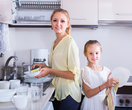 kitchen spanish: Everyday routine: happy spanish girls doing and wiping dishes in kitchen