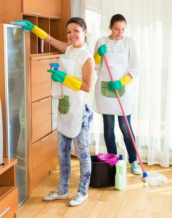 empleada domestica: Dos felices limpiadores femeninos sala de juntas de limpieza Foto de archivo