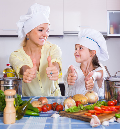 vegeterian: Excited happy adult american mom and daughter cooking vegeterian dish indoors Stock Photo