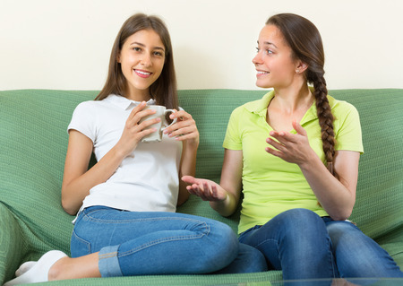 amiable: Two cheerful young girlfriends gossiping and smiling sitting on a sofa at home