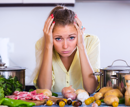frustrated: Frustrated woman looking at dinner ingredients with sad face