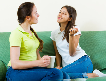 Two young women enjoying a conversation in a living room at the home