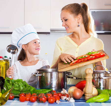 beautiful mother: Beautiful mother and little girl preparing vegetables in slow-cooker
