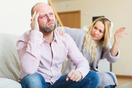 to reassure: Sad man has problem, woman consoling him on sofa. Focus on men Stock Photo