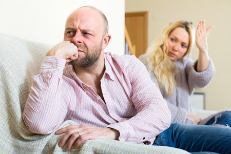 depressed man: Sad dissapointed husband sitting turned away from his wife while she waves her hand at him Stock Photo