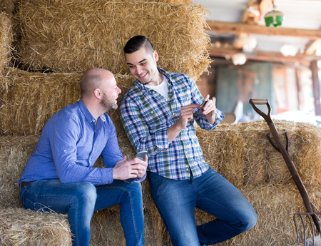 hayloft: Portrait of two positive farmers with phones at hayloft. Selective focus