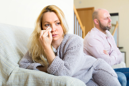 sad couple: Sad wife wiping her tears with a handkerchief after a conflict in a family. Her stressed husband in sitting in a background Stock Photo
