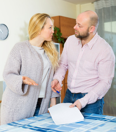 covetous: Serious wife and adult husband reading financial documents