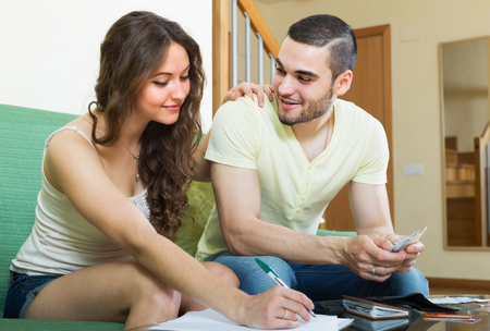 calculated: Smiling couple with money and documents  in home