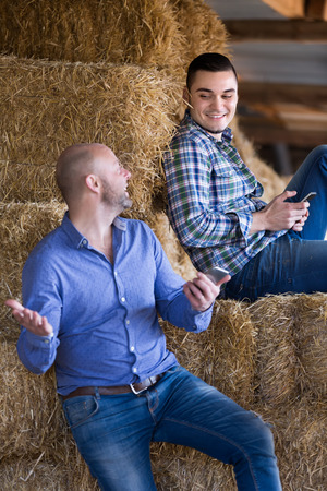 hayloft: Portrait of two smiling positive farmers with phones at hayloft. Selective focus Stock Photo