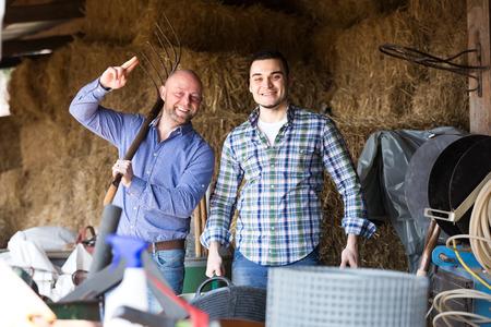 rancheros: rancheros feliz trabajando en un cobertizo lleno de aperos de labranza y el heno