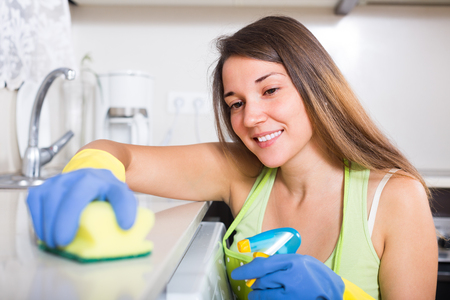 kitchen furniture: Young brunette woman in apron cleaning furniture in kitchen