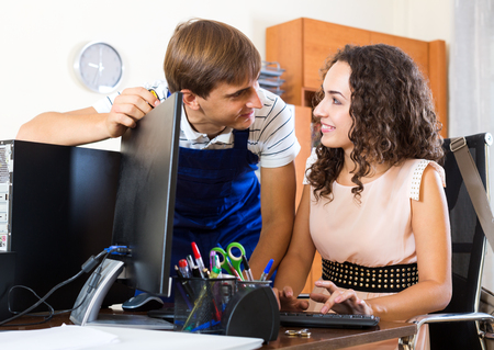 malfunction: Smiling technical support engineer doing malfunction diagnosis of client computer Stock Photo