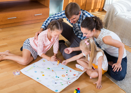 family indoors: Young smiling parents and two little daughters playing board game at home