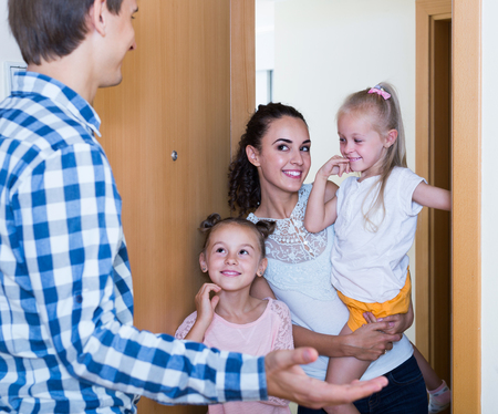 recieving: happy european adults and kids meeting at doorway and greeting one another