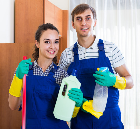 cleanup: Portrait of smiling people in overalls with supplies doing clean-up
