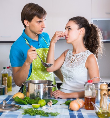 foul: Surprised spanish adults feeling foul smell of food from casserole Stock Photo