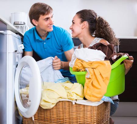 lavando ropa: El par sonriente joven cerca de la lavadora con la cesta de ropa Foto de archivo
