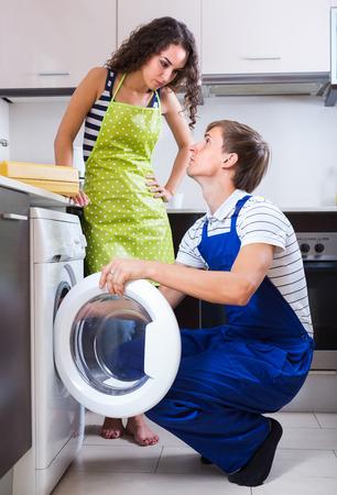 unblock: Professional mechanic repairing washing machine of sad female client Stock Photo