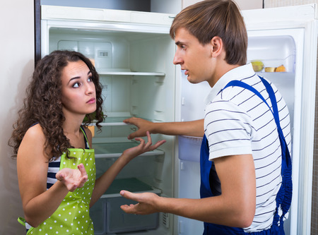 denying: Tired handyman cannot repair refrigerator at the kitchen of female client Stock Photo