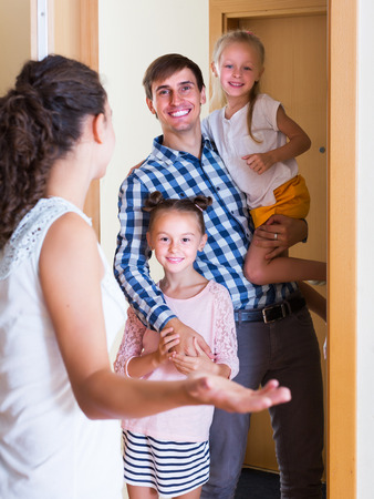 expected: Hospitable householder meeting expected guests at doorway and smiling Stock Photo