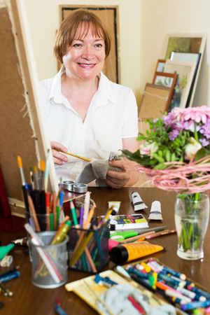 contentedness: Happy mature artist creating a new picture