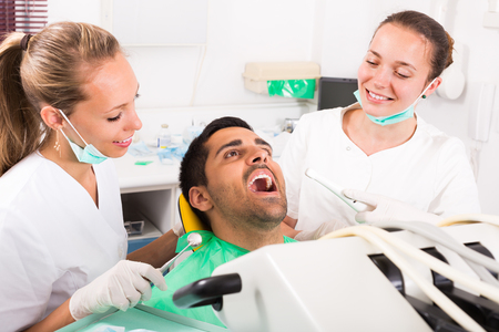 operative: Happy client and dental clinic crew during check up. Focus on man