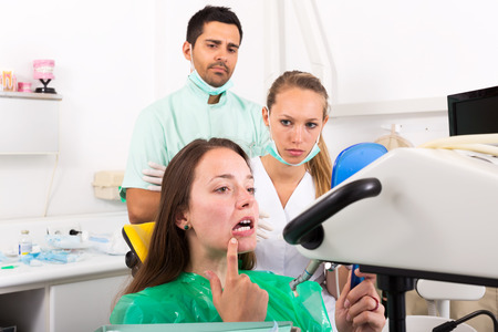 detecting: Female young patient detecting problems on inspection at the dentist. Focus on the patient Stock Photo