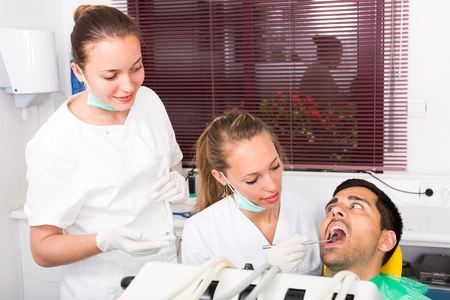 oral cavity: Female dentist with assistant examining the oral cavity of patient at dental clinic