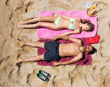 couple in love: Young couple laying on the sandy beach at the sea shore in a sunny day