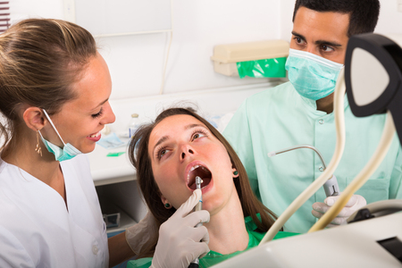 Dentist with assistant diagnostics the oral cavity of female patient